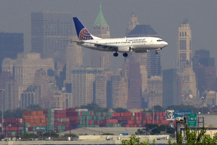 Image: An airplane prepares to land at the Newark International Airport in Newark, N.J., with lower Manhattan in the background