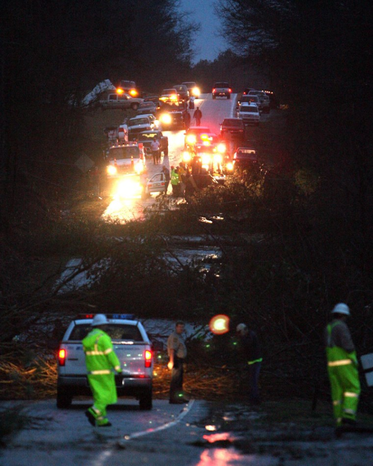 Image: Crews work to clean up downed trees in a street in Wilndham Springs, Ala