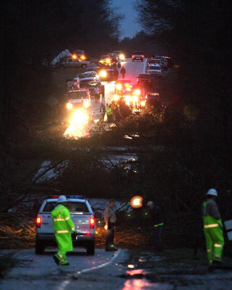 Image: Crews work to clean up downed trees in a street in Wilndham Springs, Ala