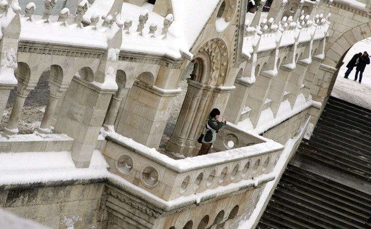 Image: A tourist takes a photo on a balcony of the Budapest's place of interest, the Fisher Bastion.