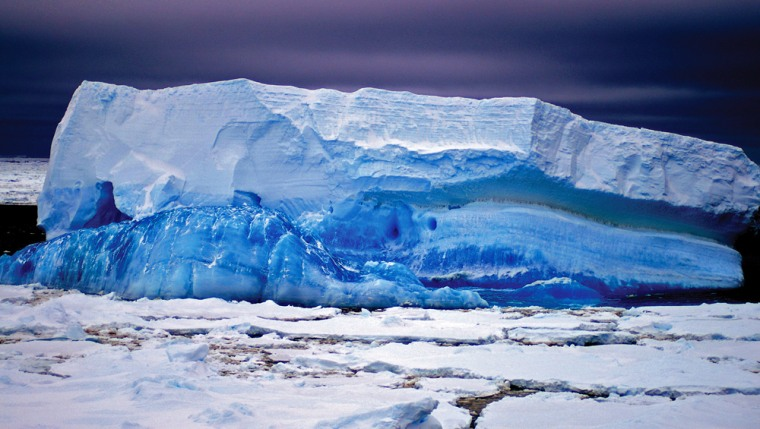Image: A blue iceberg towers out of the ice floe