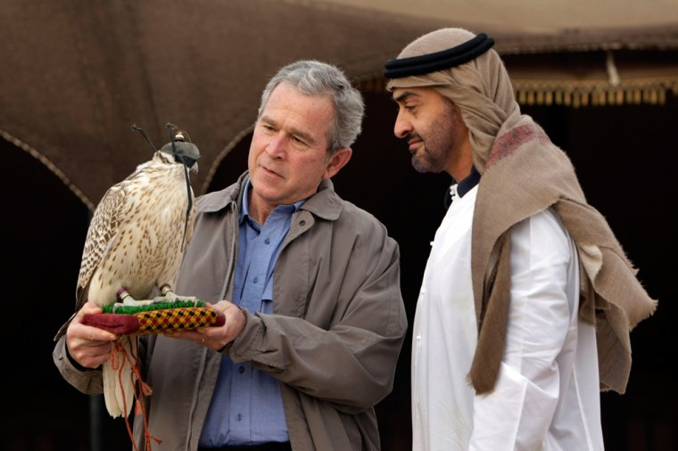 Image: US President George W. Bush, left, holds up a falcon as the Crown Prince of Abu Dhabi Sheik Mohammed bin Zayed Al Nahyan, right, watches