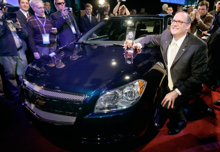 Image: Ed Peper, general manager of Chevrolet, poses next to the 2008 Car of the Year, Chevrolet Malibu