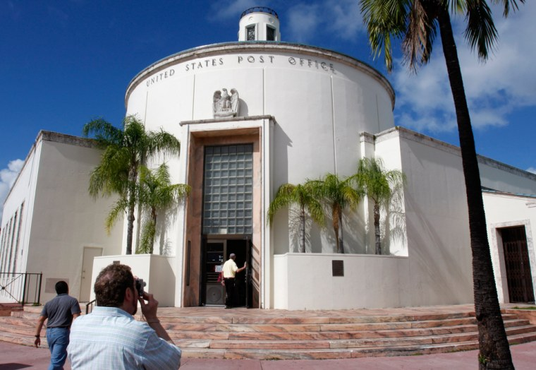 Image: A tourist photographs an art deco style U.S. Post Office built in 1937 while on a tour of the art deco district in Miami Beach, Fla.