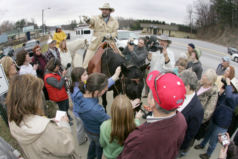 Image: Bill Inman sits atop his horse, Blackie, as he talks to a group of well wishers near the end of his ride across America