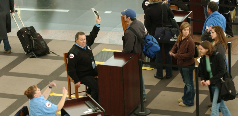 Image: An identification security screener with hand raised calls for a TSA screener
