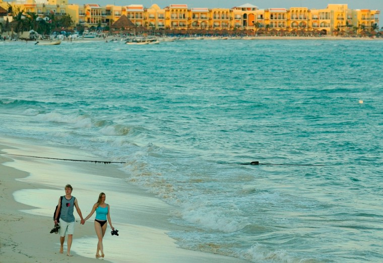 Image: A couple of tourists walk on the beach a in Playa del Carmen, south of Cancun, Mexico.