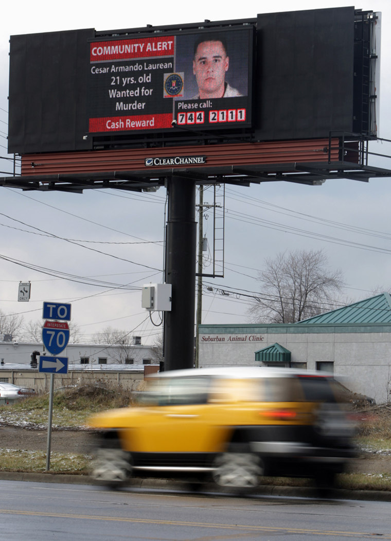 Image: Motorists drive near an electronic billboard with the picture of Cesar Laurean.