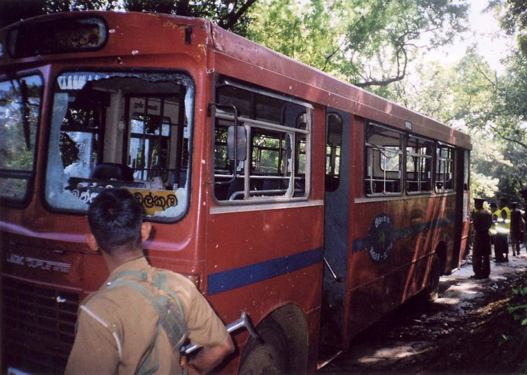 Image: Sri Lankan security personnel stand near a civilian bus which was struck by a bomb blast