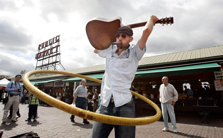 Image:  Emery Carl twirls a guitar and a hula hoop while playing a harmonica