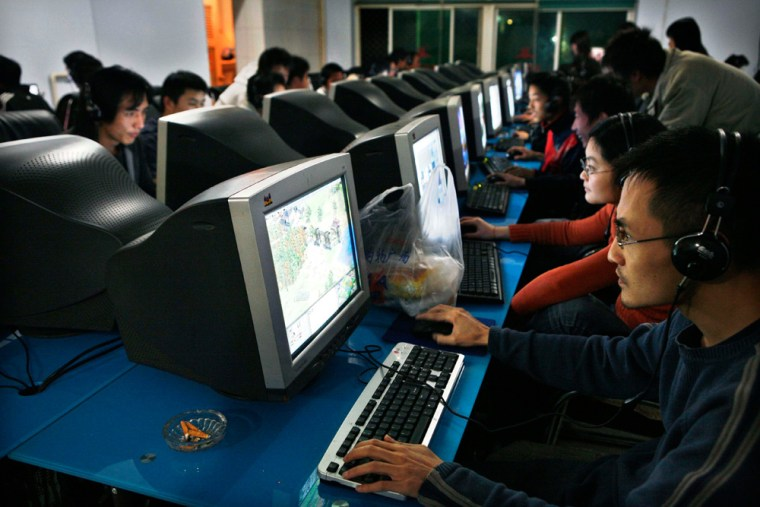 Image: People use computers in an internet cafe