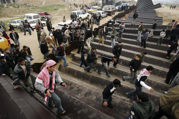 Image: Palestinians cross the Rafah border into Egypt