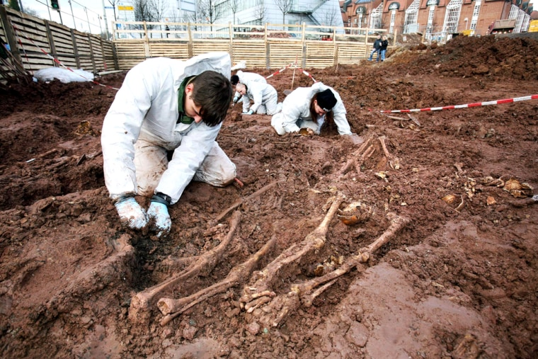 Image: Forensic experts secure evidence in a pit of a construction site in Kassel, Germany.