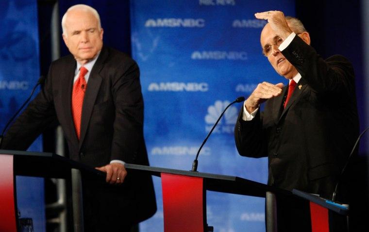 Image: US Senator John McCain listens as former New York City Mayor Giuliani speaks during GOP debate at Florida.