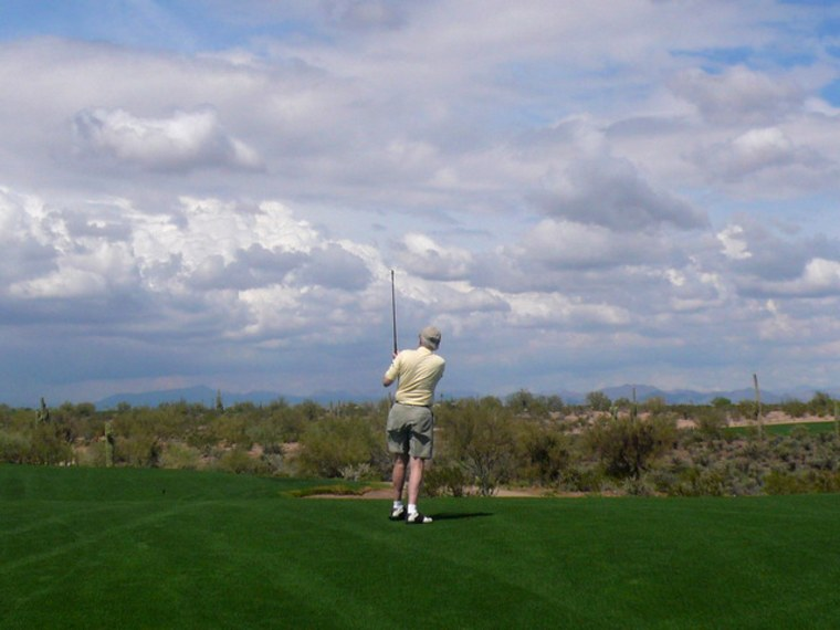 Image:  man teeing off on a golfcourse