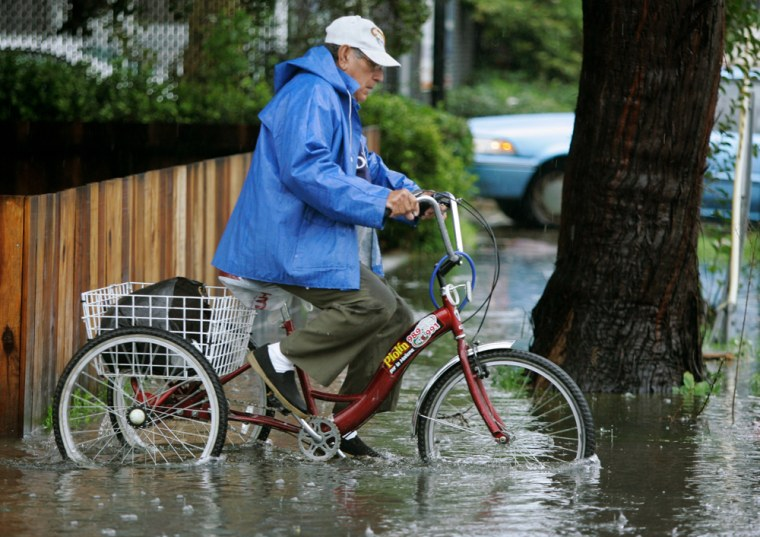 A man rides his bike through a flooded street in Palo Alto, Calif., during a rain storm on Friday.Streets flooded, hillsides slipped and commuters cursedduring powerful rain and snow storms that lashed Southern California.