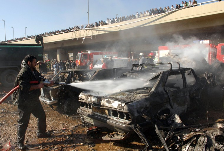 Image: A firefighter extinguishes burning cars at the site of explosion in Beirut.