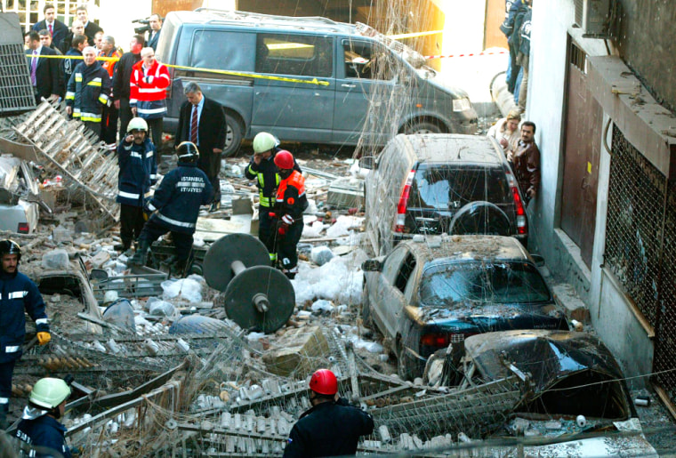Image: Firemen stand amid rubble after an explosion in a factory