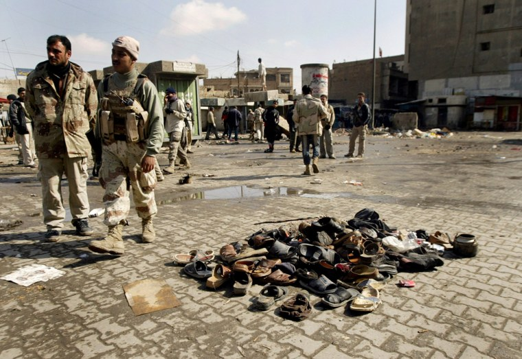 Image: Iraqi soldiers walk past a pile of slippers