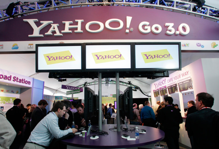 Image: People look over displays at the Yahoo! booth.