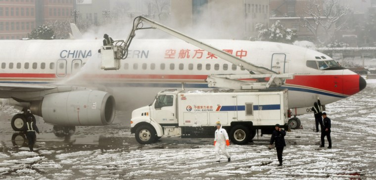 Image: Airport workers remove snow and ice from a  plane