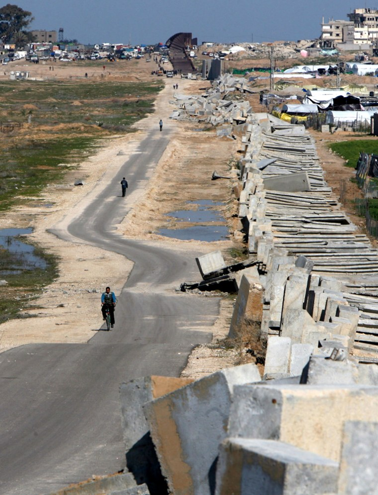 Image: Palestinians walk along a section of the destroyed border fence