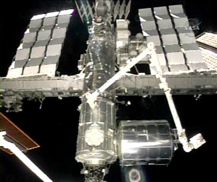 This image from NASA Television shows the European Space Agency's Columbus module, at lower right, attached to the International Space Station on Tuesday. The module was lifted from the payload bay of the shuttle Atlantis on Monday and installed during a spacewalk.