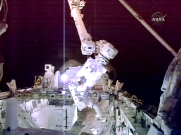 Spacewalkers Rex Walheim and Stanley Love floated out of the hatch to install experiments andretrieve an old space station gyroscope.