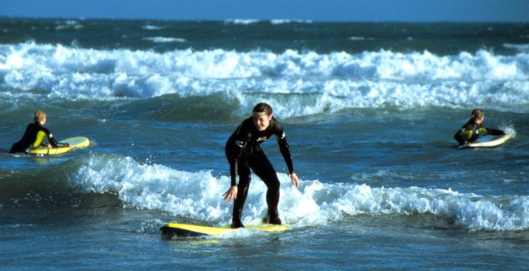 Image: surfers at Tramore Beach in Waterford, Ireland