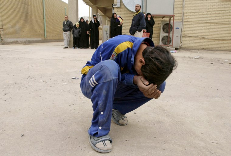 Image: An Iraqi boy cries outside a hospital morgue in Baghdad as he waits to collect his relative's body.
