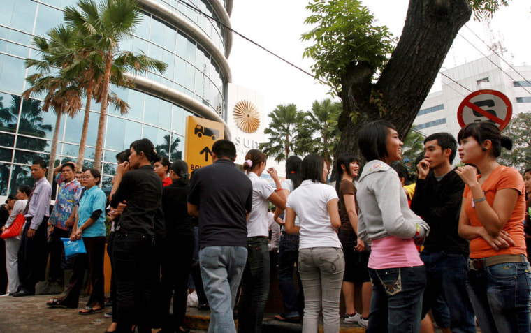 Image: Employees and mall goers evacuate to the open air for safety in Medan.