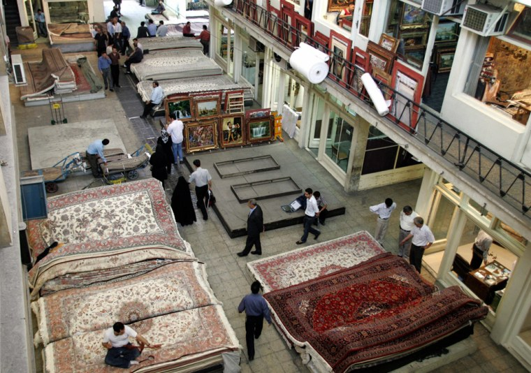 Image: Iranians browse through piles of Persian carpets