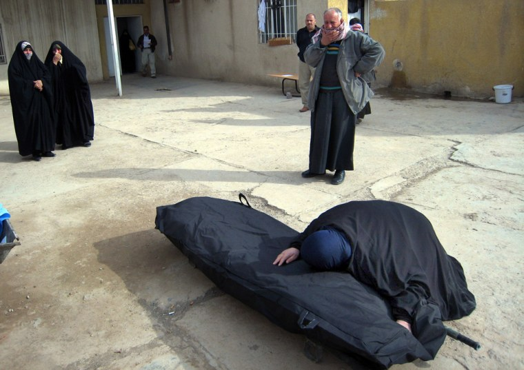 Image: An Iraqi woman weeps over the body of a relative