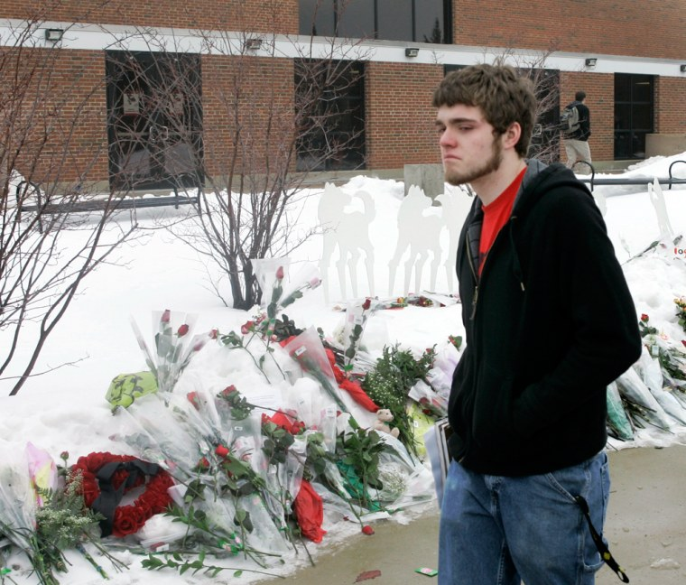 Image: A Northern Illinois University student walks away from a small memorial outside Cole Hall