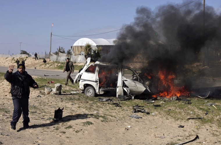 Image: A Palestinian man stands next to a burning car in Khan Younis southern Gaza Strip