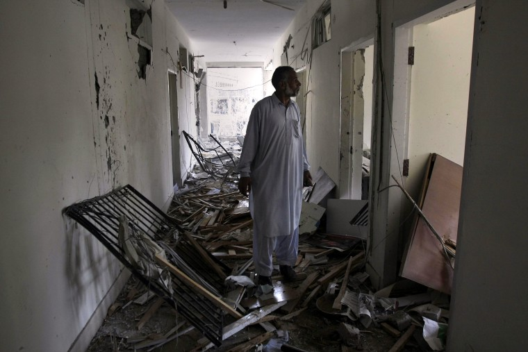 Image: An official of the Federal Invesigation Agency looks at the damage to his office building after a suicide bombing in Lahore on March 12.