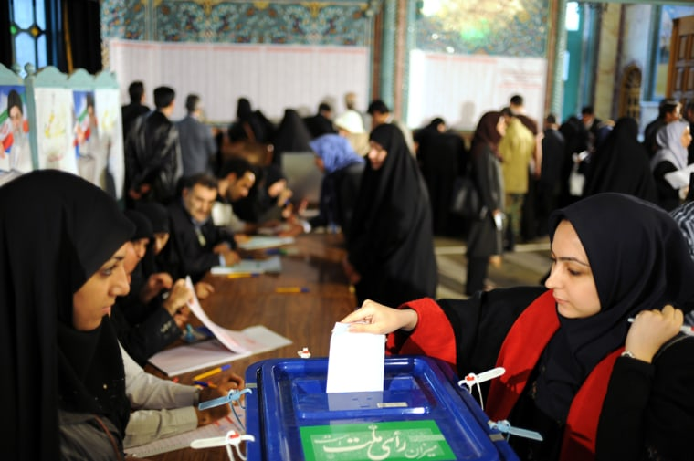 Image: Iranian woman casts her ballot at a polling station in Tehran