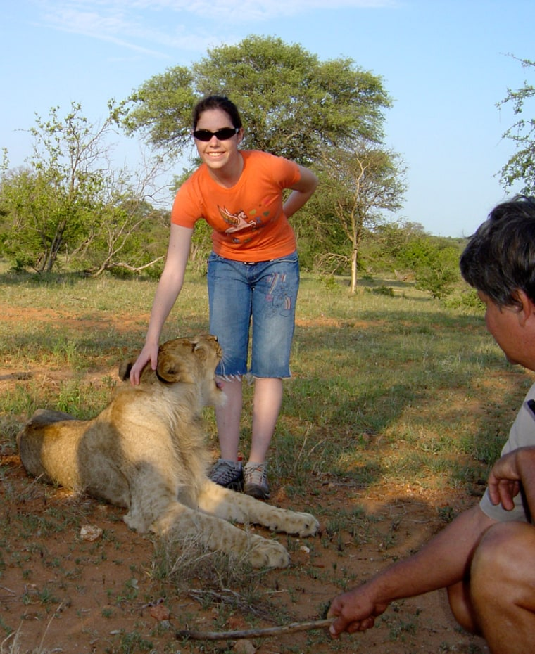 Image: Ashley Kahn standing beside a 6 month-old male lion cub
