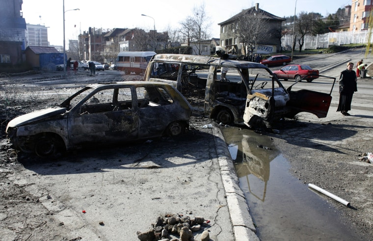 Image: A woman walks by burnt vehicles in the ethnically divided city of Mitrovica