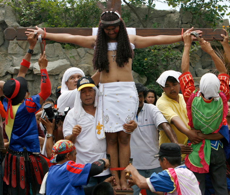 Image: Residents nail a penitent to a wooden cross.