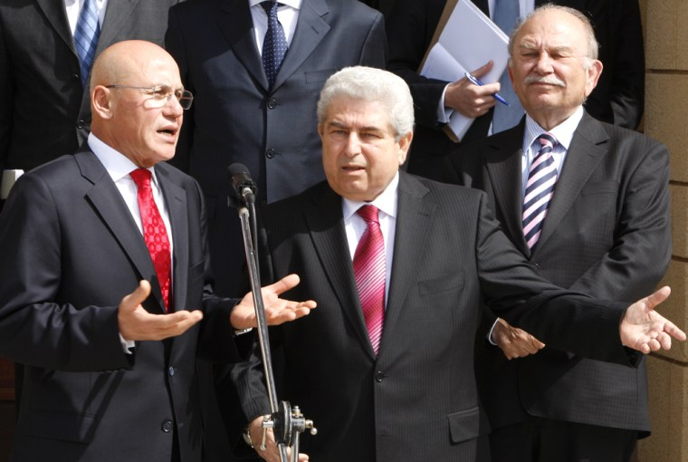 Greek Cypriot Leader Dimitris Christofias speaks with Turkish Cypriot Leader Mehmet Ali Talat at the end of their first meeting in Nicosia