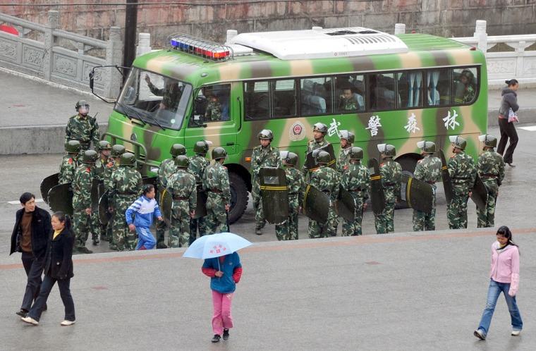 Image: Tibetans walk past Chinese paramilitary policemen patrolling in Kangding county, the capital of Ganzi Tibetan Autonomous Prefecture