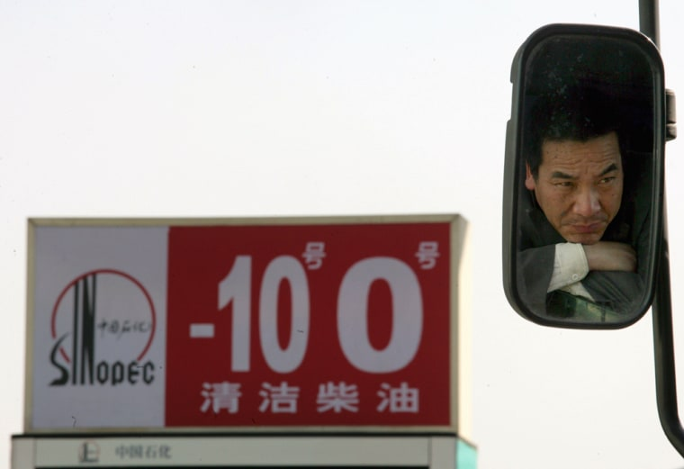 Image: A Chinese truck driver is seen in a back mirror while waiting outside a Sinopec gas station.