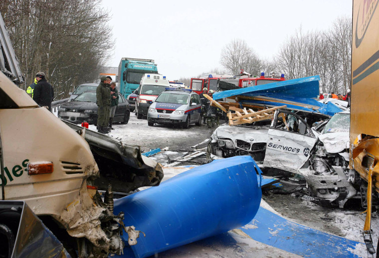 Image: Rescue personnel are seen next to the wreckage of vehicles.