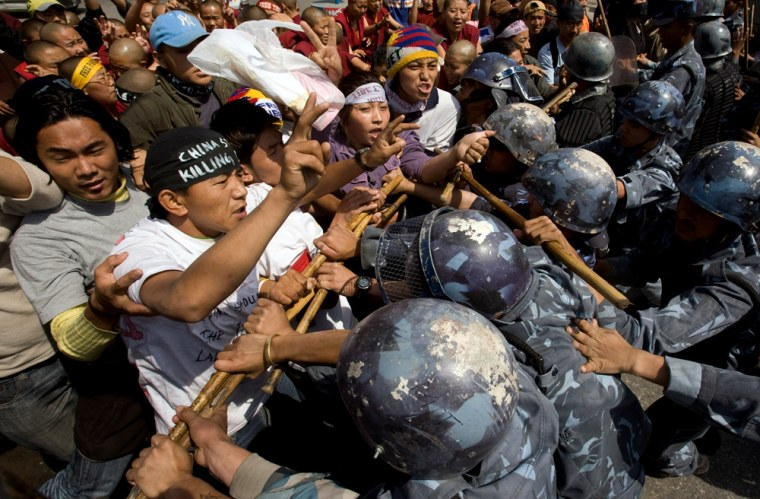 Riot police try to stop Tibetan activists from protesting outside the visa section of the Chinese embassy in Kathmandu