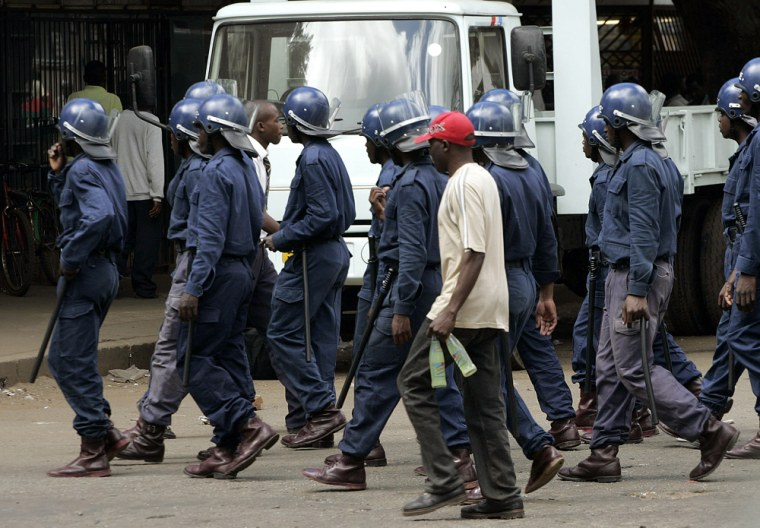 Image: Zimbabwe riot police patrol the city centre in the capital Harare