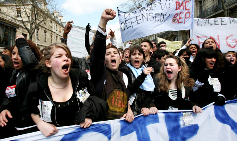 Image: Students show banners and shout slogans during a demonstration