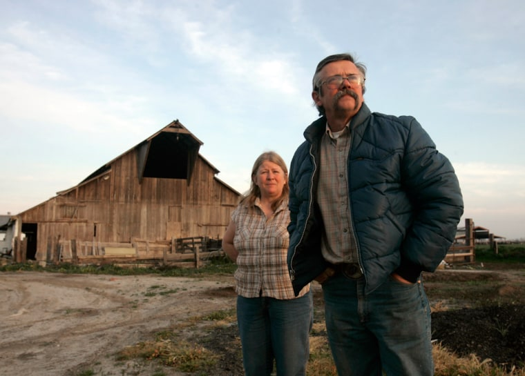 Image: Joe and Janice Pimentel stand near a barn on their dairy near Atwater, Calif.