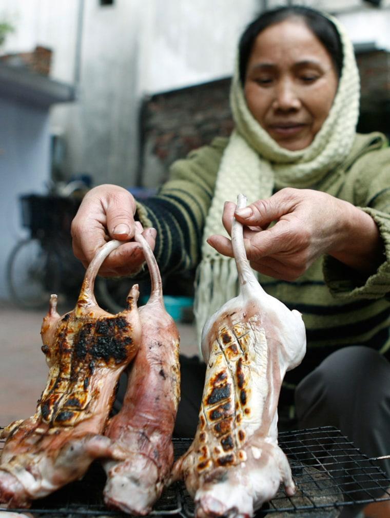 Image: A woman grills rats at Dinh Bang village, outside Hanoi