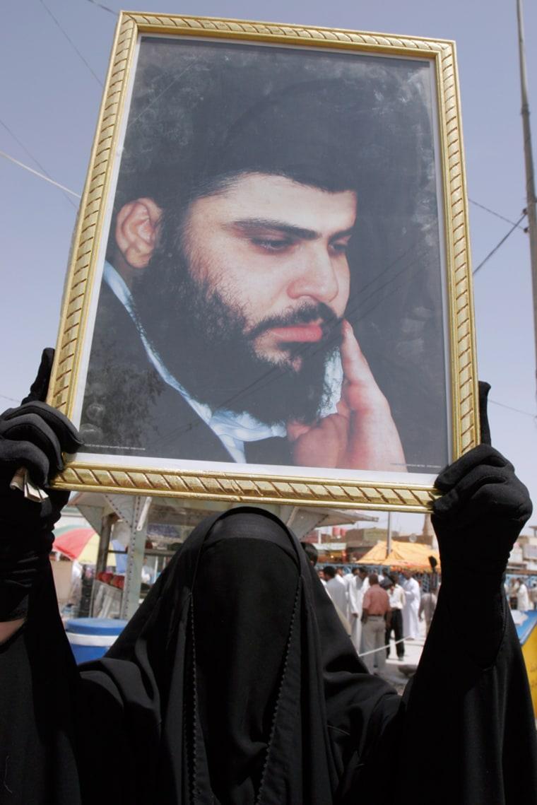 An Iraqi Shiite woman raises a portrait of radical cleric Muqtada al-Sadr in the city of Najaf on Friday.